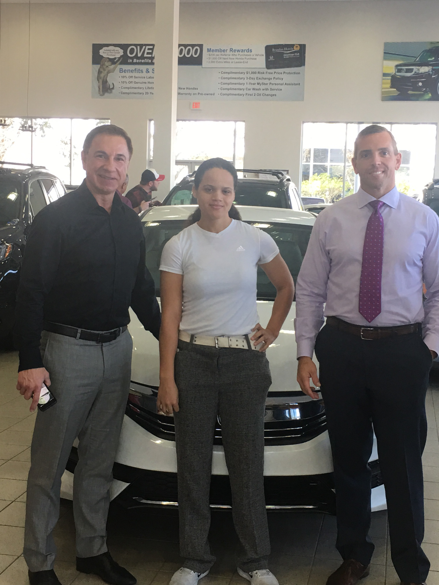 John Marazzi (L) and Sam Raabe (R) congratulate Alexis R. for winning the new 2017 Honda Accord